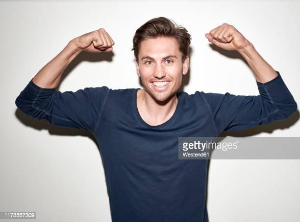portrait of laughing man flexing muscles - langärmlig stock-fotos und bilder