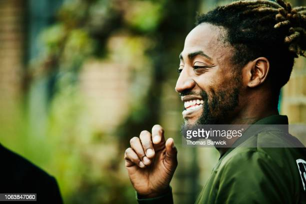 portrait of laughing man hanging out with friends - modern manhood stock pictures, royalty-free photos & images