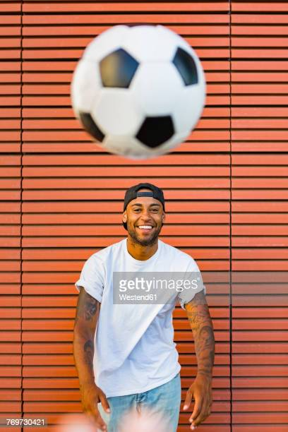 Portrait of laughing man having fun with soccer ball