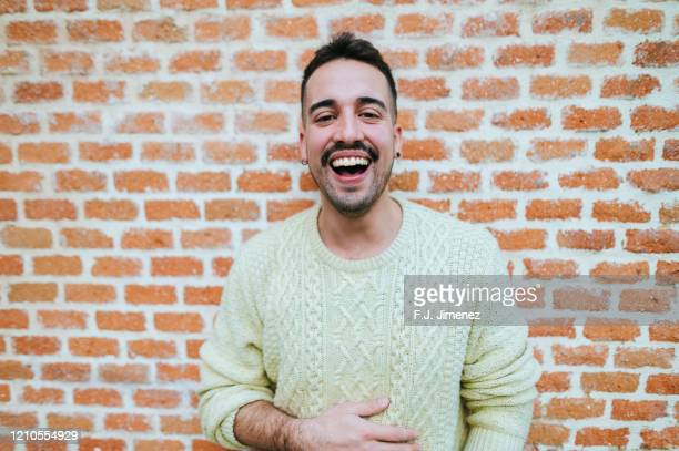 portrait of laughing man in front of brick wall - comedian stock pictures, royalty-free photos & images