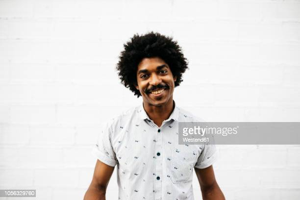 portrait of laughing man in front of white wall - big hair stock photos and pictures