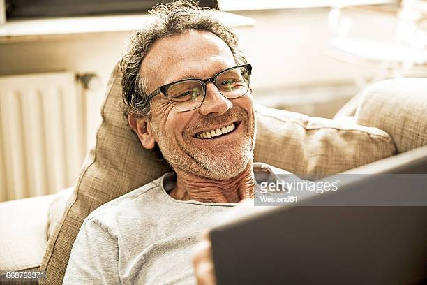 Portrait of laughing man lying on the couch using tablet