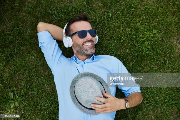 portrait of laughing man relaxing on a meadow listening music with headphones, top view - one mid adult man only stock pictures, royalty-free photos & images