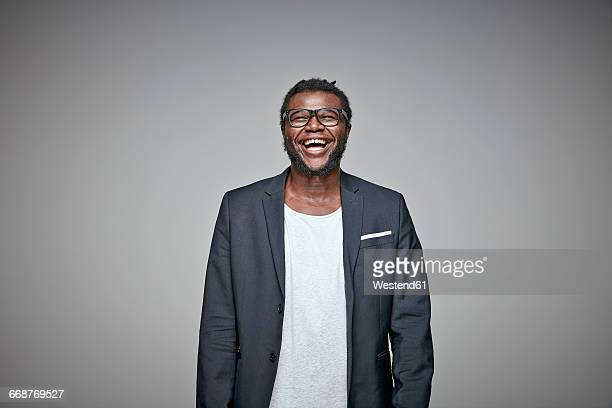portrait of laughing man wearing glasses and jacket - black jacket stock pictures, royalty-free photos & images