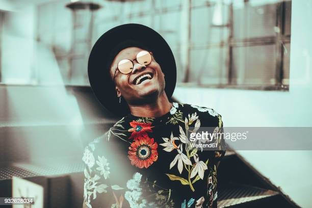 portrait of laughing man wearing hat, sunglasses and black t-shirt with floral design - sombrero negro fotografías e imágenes de stock