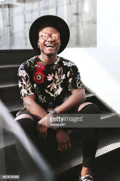 Portrait of laughing man wearing hat, sunglasses and black t-shirt with floral design sitting on stairs