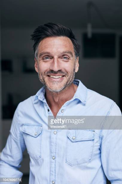 portrait of laughing man wearing light blue denim shirt - 45 49 jahre stock-fotos und bilder