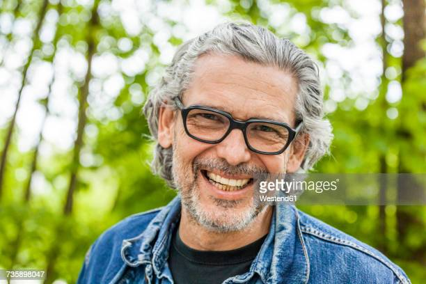 Portrait of laughing man with grey hair and beard wearing glasses