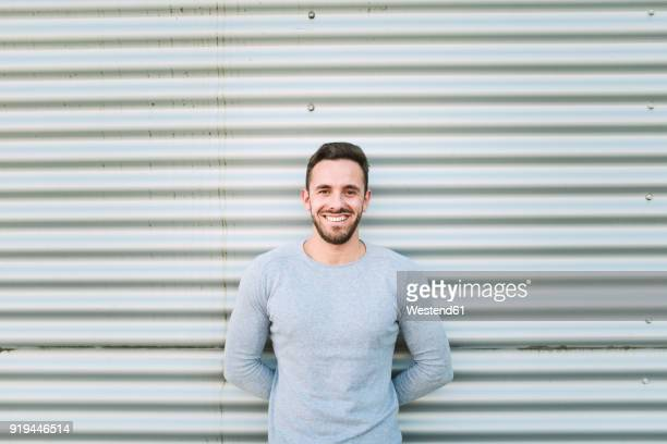 portrait of laughing man with hands behind his back - long sleeved stock pictures, royalty-free photos & images