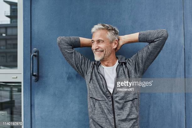 portrait of laughing mature man in front of gym - hände hinter dem kopf stock-fotos und bilder