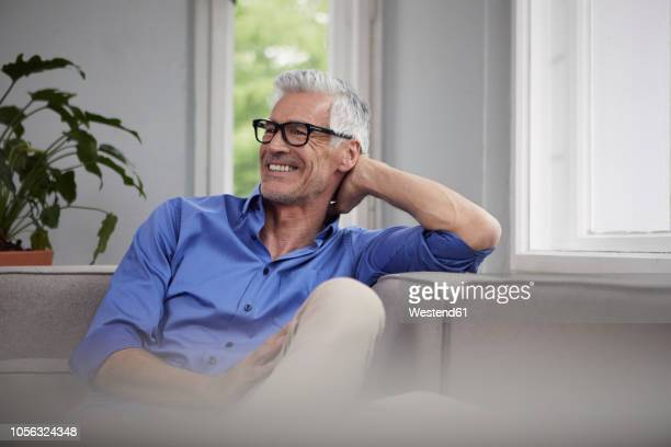 portrait of laughing mature man sitting on couch at home - serene people stock pictures, royalty-free photos & images
