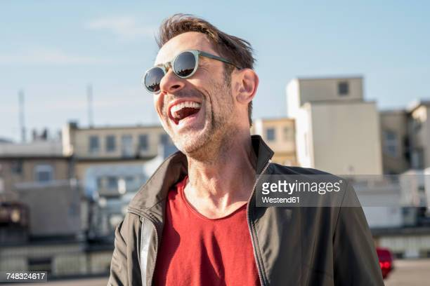 portrait of laughing mature man with stubble wearing sunglasses - lachen stock-fotos und bilder