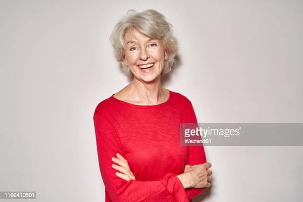 portrait of laughing mature woman wearing red pullover - quinquagénaire photos et images de collection
