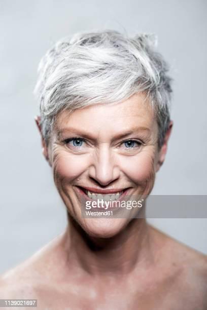 portrait of laughing mature woman with short grey hair and blue eyes - medelålders kvinnor naken bildbanksfoton och bilder