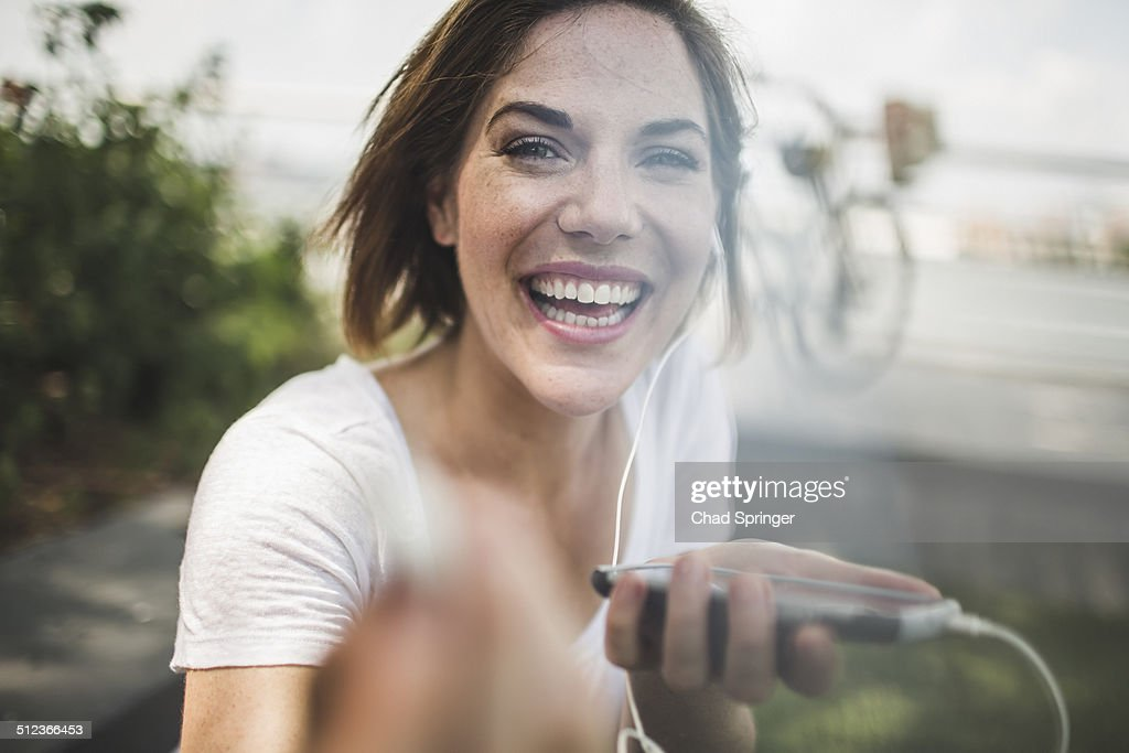 Portrait of laughing mid adult woman holding up earphone : Stock Photo