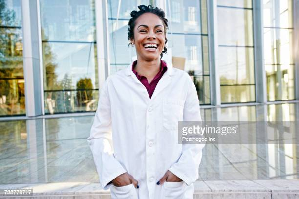 portrait of laughing mixed race doctor outdoors at hospital - laborkittel stock-fotos und bilder