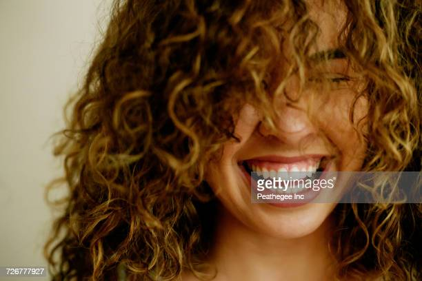 portrait of laughing mixed race woman - curly stock pictures, royalty-free photos & images