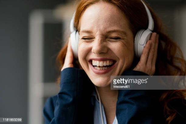 portrait of laughing redheaded businesswoman listening music with white headphones - luisteren stockfoto's en -beelden