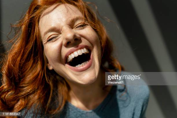 portrait of laughing redheaded woman - lachen stock-fotos und bilder
