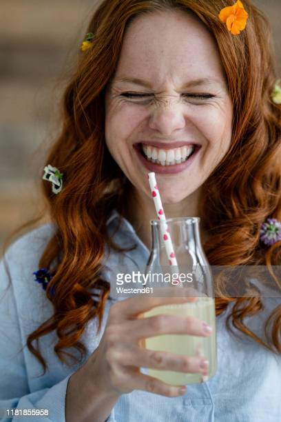 portrait of laughing redheaded woman with blossoms in hair drinking lemonade - cold drink stock pictures, royalty-free photos & images