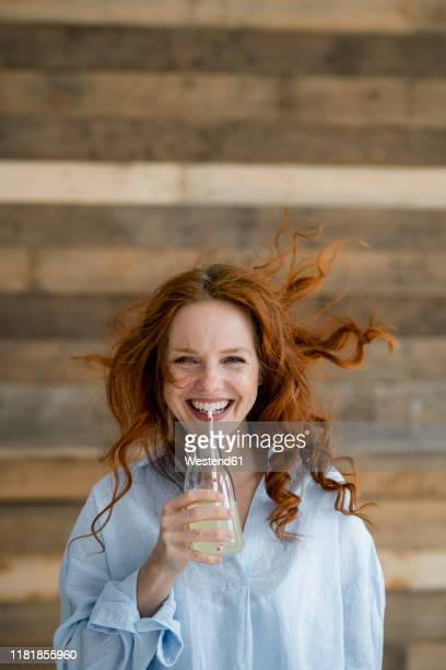 portrait of laughing redheaded woman with blowing hair drinking lemonade - kaltes getränk stock-fotos und bilder