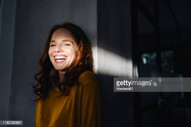 portrait of laughing redheaded woman with light and shadow - lachen stock-fotos und bilder