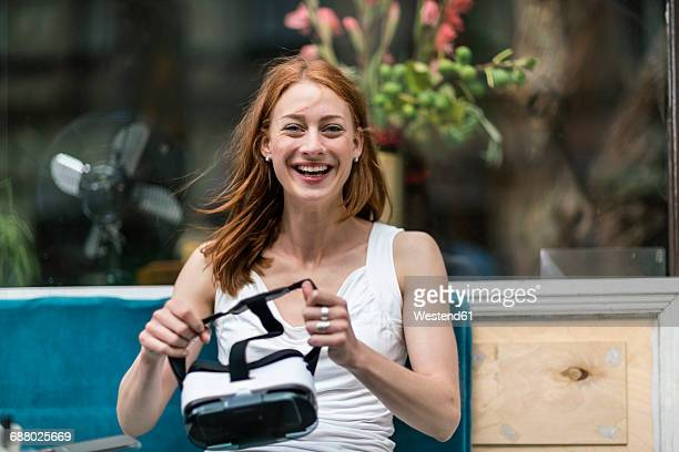 Portrait of laughing redheaded woman with Virtual Reality Glasses