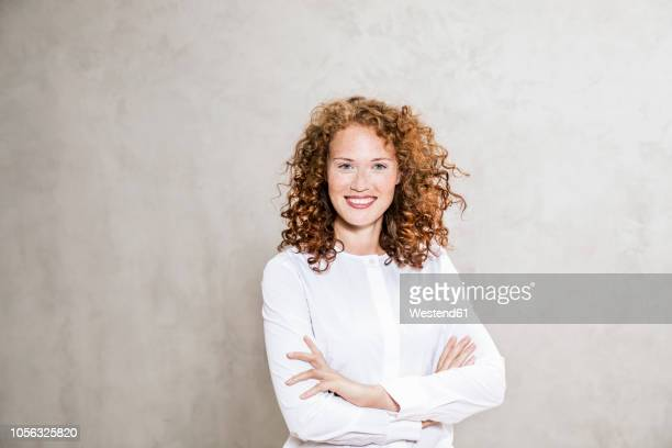 portrait of laughing redheaded young woman with arms crossed - redhead stock pictures, royalty-free photos & images