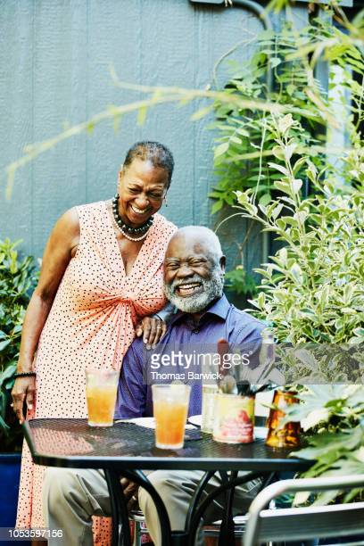 portrait of laughing senior couple at outdoor cafe on summer afternoon - candid cleavage stock pictures, royalty-free photos & images