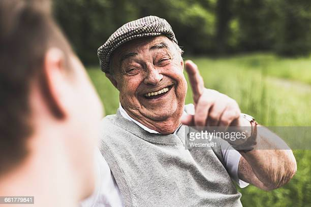 portrait of laughing senior man talking to his grandson - lachen stock-fotos und bilder