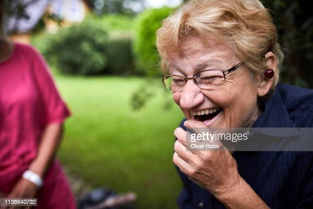 portrait of laughing senior woman in garden - old lady funny stock pictures, royalty-free photos & images