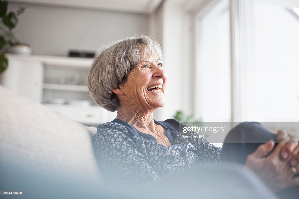 Portrait of laughing senior woman sitting on couch at home : Foto stock