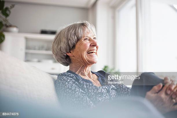 portrait of laughing senior woman sitting on couch at home - seniore vrouwen stockfoto's en -beelden
