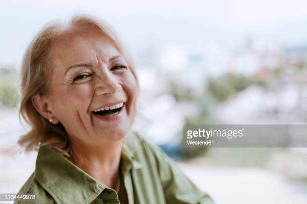 portrait of laughing senior woman with hearing aid outdoors - relief emotion stock pictures, royalty-free photos & images
