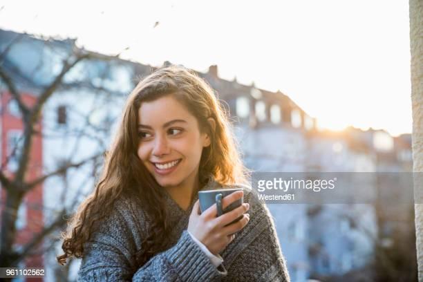 Portrait of laughing teenage girl with coffee mug on balcony at twilight