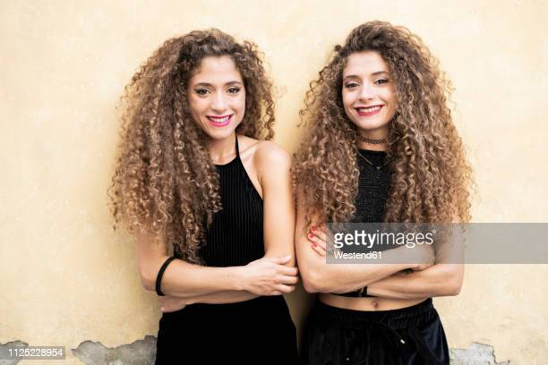 portrait of laughing twin sisters standing side by side - gleichheit stock-fotos und bilder