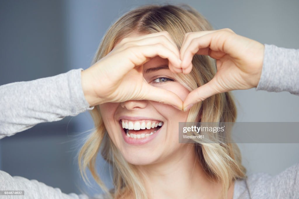 Portrait of laughing woman building heart with her fingers : Stock-Foto
