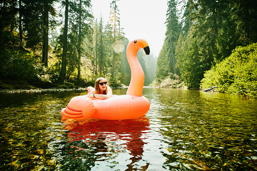 Portrait of laughing woman floating down river on inflatable pink flamingo - gettyimageskorea