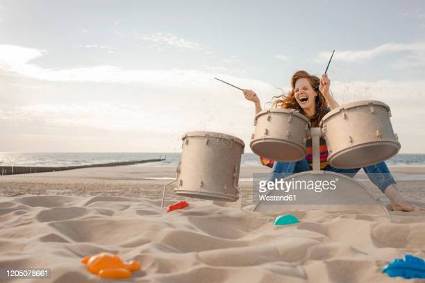 portrait of laughing woman playing drums on the beach - truncheon stock pictures, royalty-free photos & images