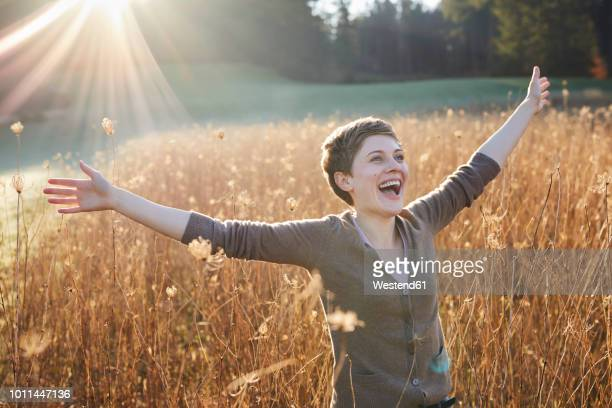 portrait of laughing woman relaxing in nature - arms outstretched stock pictures, royalty-free photos & images