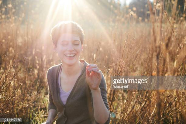 portrait of laughing woman relaxing in nature - gegenlicht stock-fotos und bilder