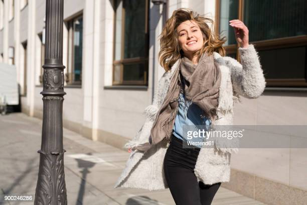 portrait of laughing woman running on pavement - schal stock-fotos und bilder