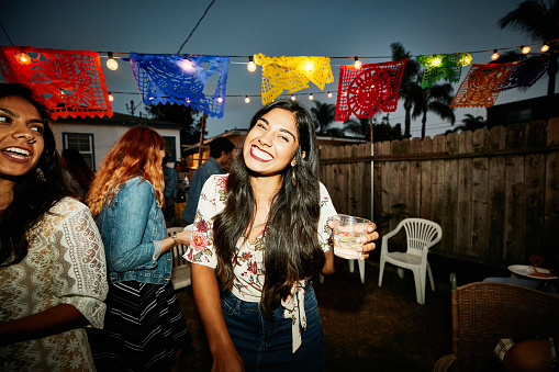 Portrait of laughing woman sharing drinks with friends in backyard on summer evening - gettyimageskorea