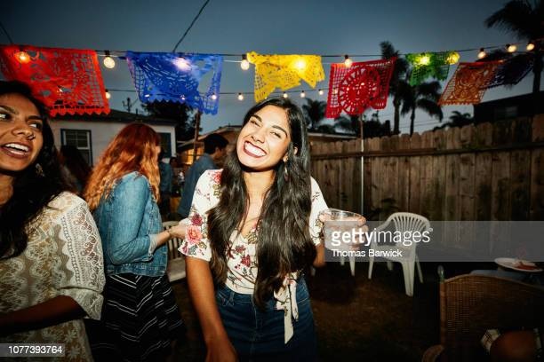 portrait of laughing woman sharing drinks with friends in backyard on summer evening - party fotografías e imágenes de stock