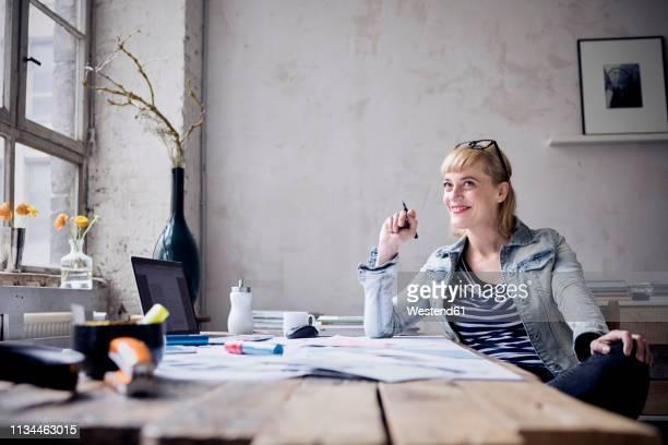 portrait of laughing woman sitting at desk in a loft - despreocupado fotografías e imágenes de stock