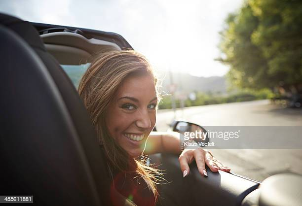 portrait of laughing woman sitting in car - klaus vedfelt mallorca stock pictures, royalty-free photos & images