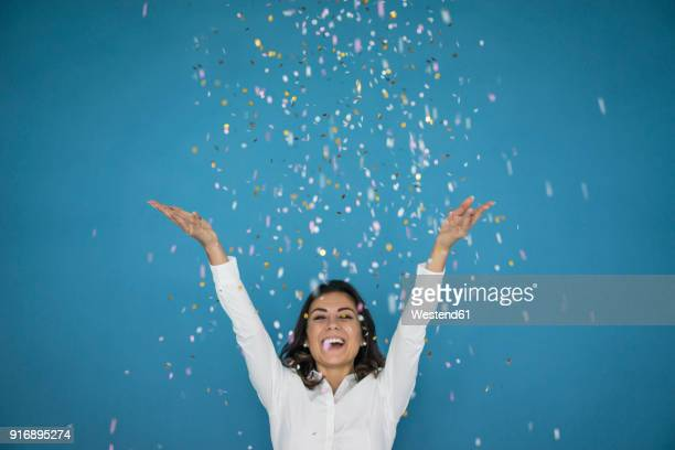 portrait of laughing woman throwing confetti in the air - festeggiamento foto e immagini stock