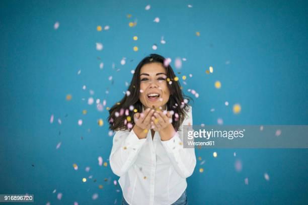 portrait of laughing woman throwing confetti in the air - leggerezza foto e immagini stock