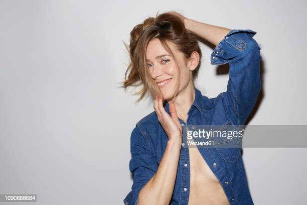 Portrait of laughing woman wearing fully unbuttoned denim shirt