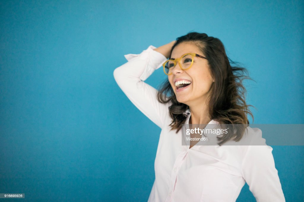 Portrait of laughing woman wearing glasses in front of blue background : Stock Photo